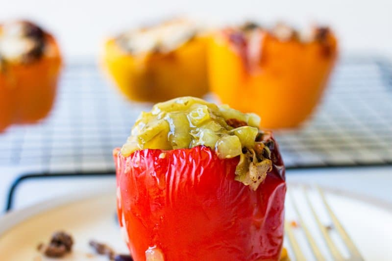 Stuffed red pepper in the front center with yellow peppers in the background.