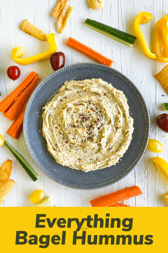 Everything bagel hummus in center. top down view. Raw veggies surrounding it. bottom part title of post with yellow background.