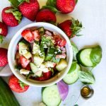 Top down view of cucumber strawberry salad with ingredients around it on the table.