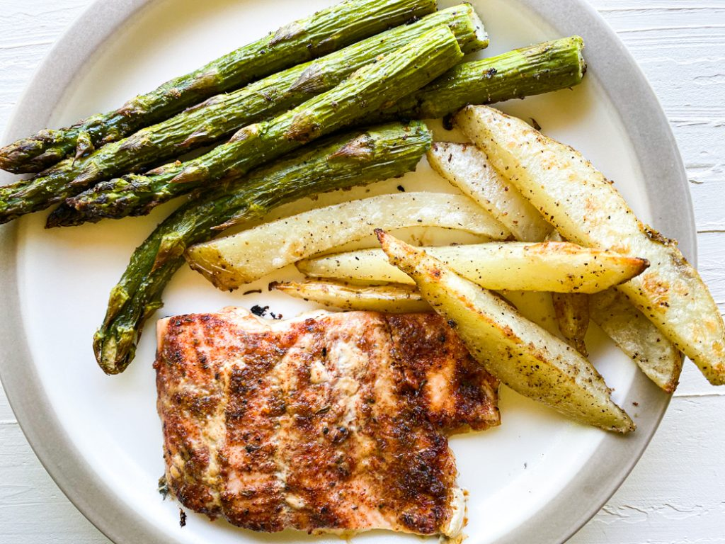 plate with maple cajun baked salmon, potatoes, and asparagus spears.