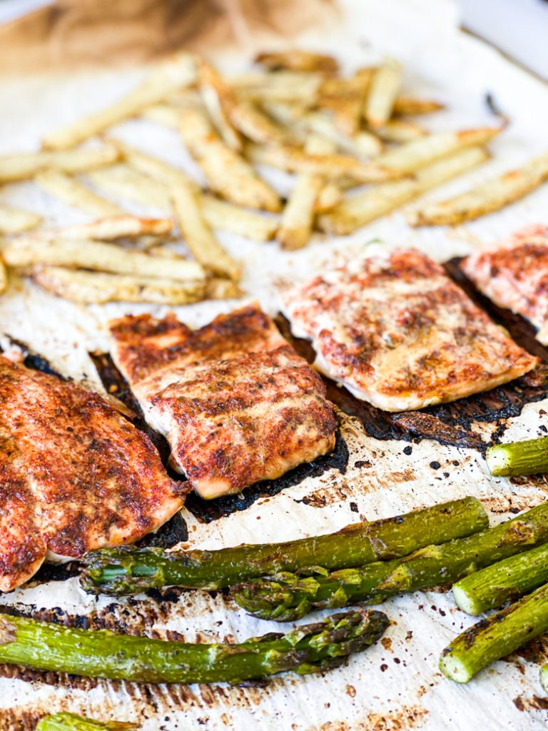 baked maple cajun salmon with potatoes and asparagus on parchment paper covered sheet pan