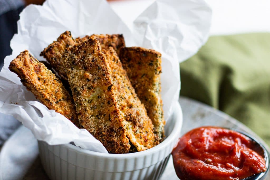 Air fryer zucchini fries in basket with side of marinara sauce